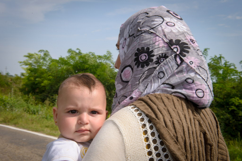 Eight-month-old Rashnee peers over her mother's shoulder. The family is one of the many migrants on the long trek through Europe after fleeing their home in Syria. PHOTO: World Vision/Laura Reinhardt