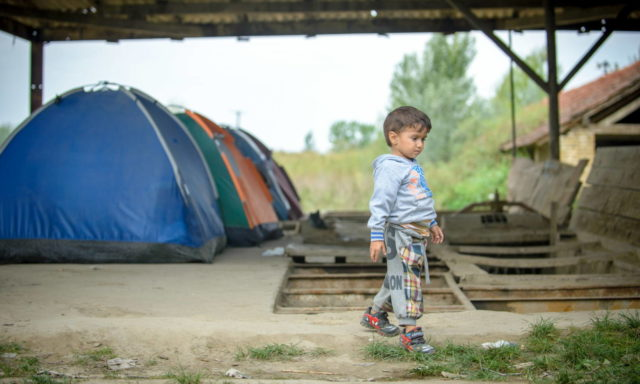Adib, 3, walks by the tents where his family and another family, all refugees, lived at an abandoned brick factory on the outskirts of the Serbian city, Subotica. The brick factory holds dangers, especially for children, such as the open pits right behind him where a child could easily fall and injure him or herself. (©2015 World Vision, Laura Reinhardt)