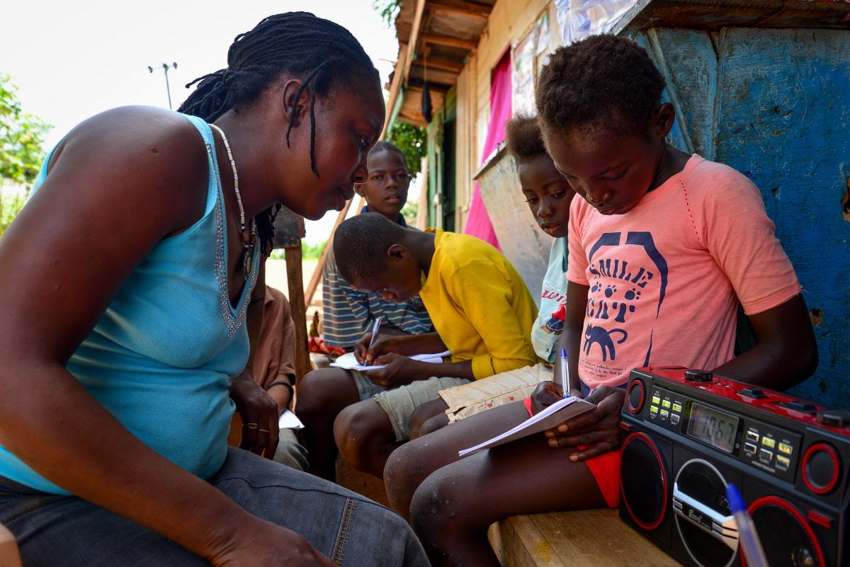Children in Sierra Leone listen to a radio program about Ebola prevention.