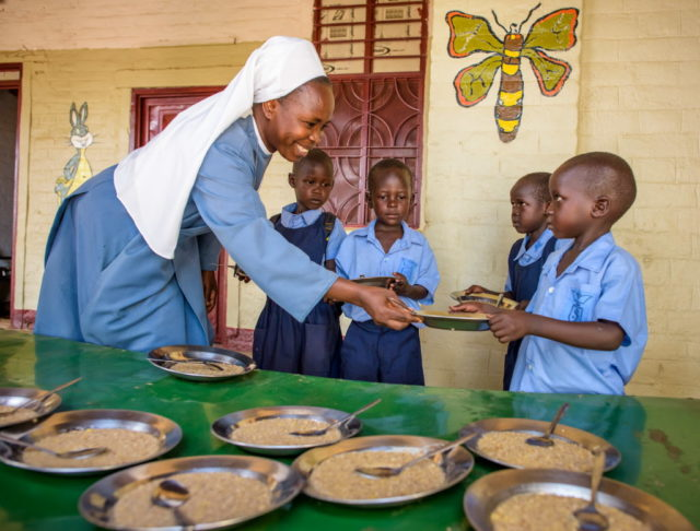 Sister Margaret hands out bowls of food to children at St. Joseph School in Kuajok, one of many