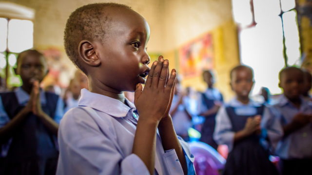 Child praying in a classroom. South Sudan, Warrup state, Kuajok.