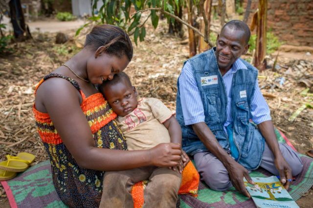 Christine Mutesi, 29, holds her daughter, Josephine Nakalembe, 2 years and 8 months old. Without the timely intervention of village health worker Matthew Nyanzi, (right), the child could have died from typhoid. Matthew is one of more than 9,000 health workers in Uganda trained by World Vision. (©2014 World Vision, Jon Warren)