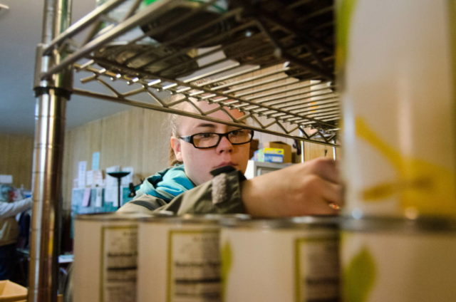 A woman stocks canned food at the Darrington, Wash. food bank. The USDA says fewer families in the U.S. experienced hunger in 2015 than the year before. (©2014 World Vision/photo by Chris Huber)