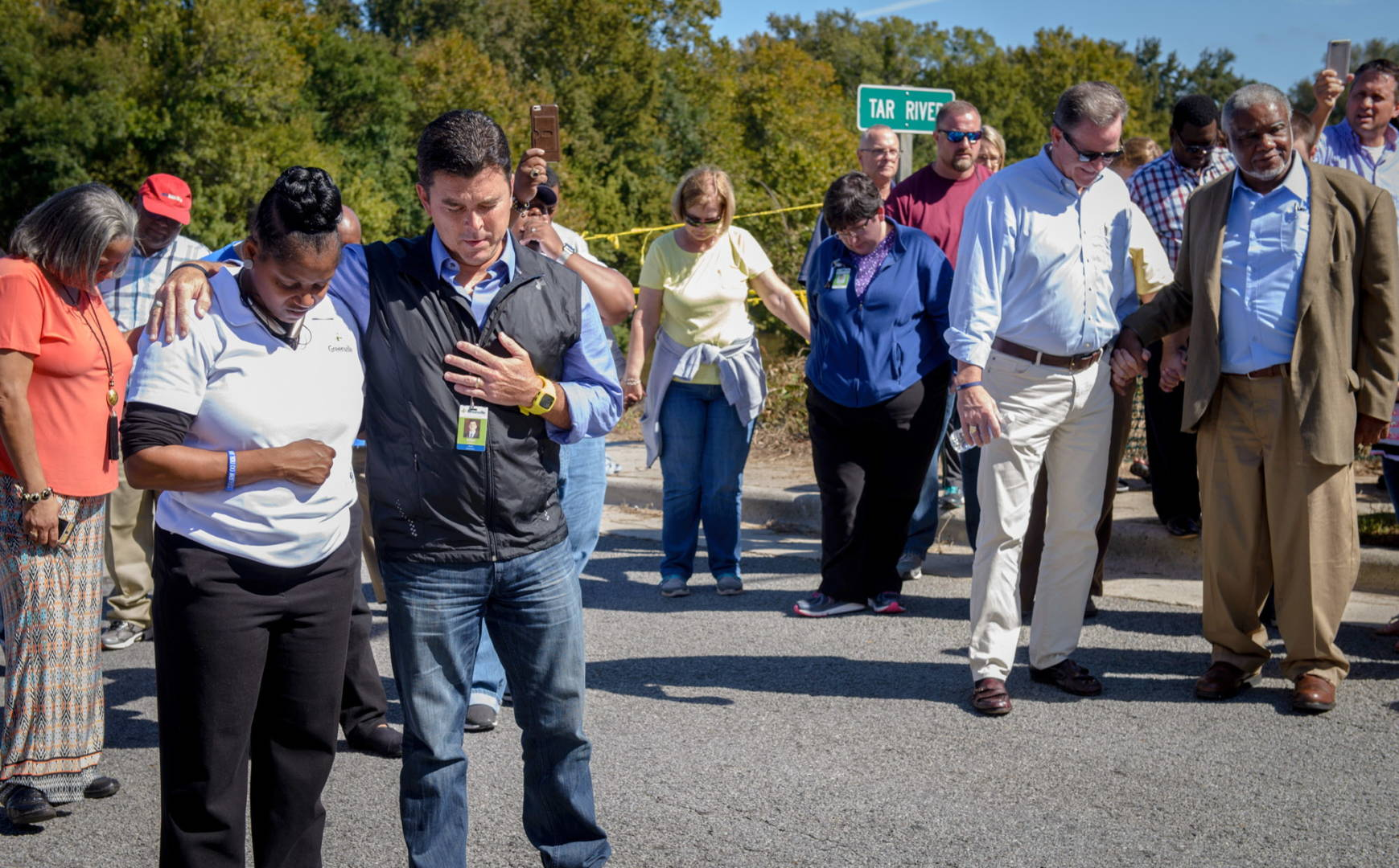 Mayor Thomas Allen (black vest) and citizens of Greenville, N.C., hold a prayer meeting next to the Tar River as the river rises after Hurricane Matthew. (©2016 World Vision, Laura Reinhardt)