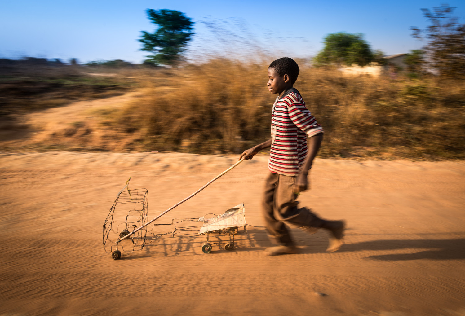Felix Kansapato, 13, pushes a toy truck made out of wire and cardboard down a road in Kapululwe, Zambia. Felix created something from nothing, using only the materials available: scrap pieces of wire, cardboard, and old wooden wheels. ©2015 Eugene Lee/World Vision