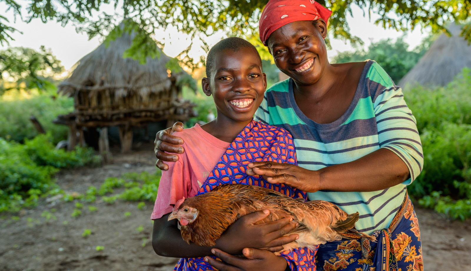 Resheal, holding a chicken, with his mother, Esnart. The chicken is an offspring of chickens his mother got through the Gift Catalog.