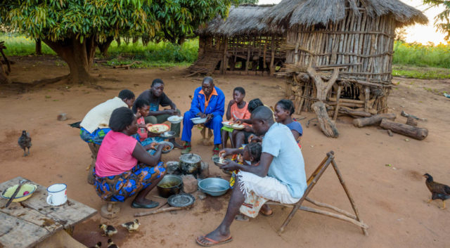 A family eats a meal at their home in Zambia. A new World Food Program study shows the growing food disparity between developing and wealthy nations. (©2016 World Vision/photo by Jon Warren)