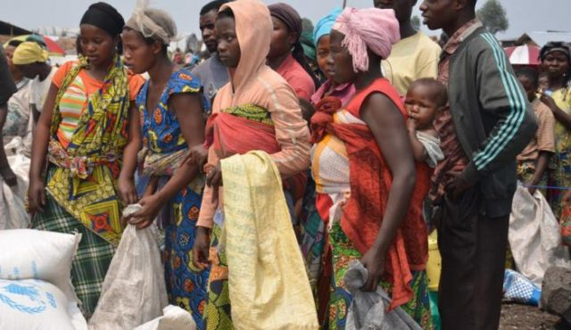 Internally displaced people queue in the camp at Mugunga