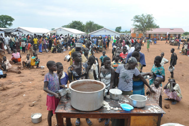 South Sudanese refugees line up for a hot meal distributed by World Vision at Nyumanzi refugee transit center in Uganda. (2016, World Vision, Moses Mukitale)