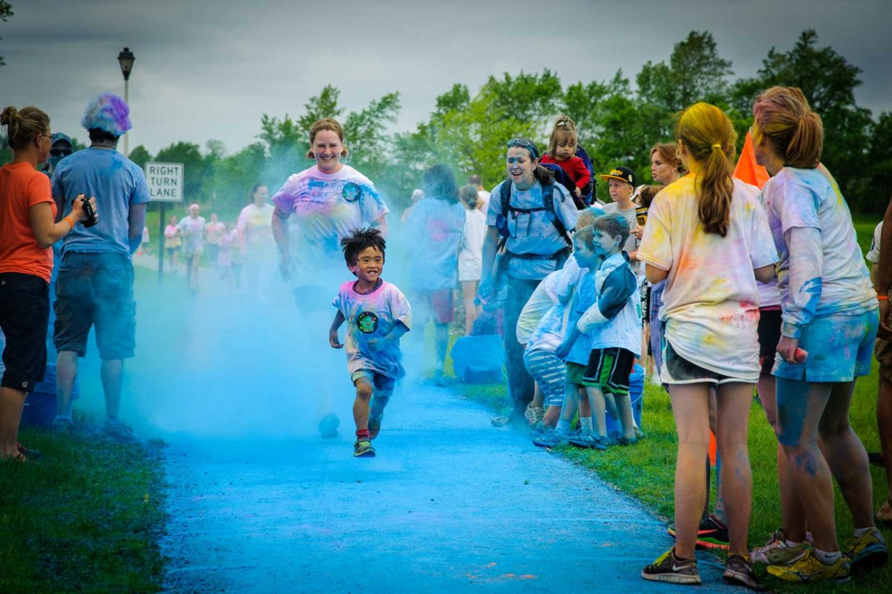 """Ezekiel and his mom Rachael race to the finish line in a 5K color dash in Saint Peter, Minnesota, in June, 2013. The event was organized by """"Livestock,"""" a non-profit music festival, founded by Jill and Alex Hass, to provide animals through World Vision's Gift Catalog. """"This was our first color dash,"""" says Rachel. """"The picture captures his attitude toward life."""" She added that """"Loving others and helping them is central to our goal to further Christ's Kingdom by showing love. Running the race, and donating money toward World Vision and other charities is important to us because it helps us think outside of ourselves."""""""