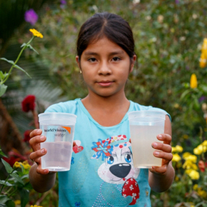 Girl holds glass of clean water and glass of dirty water.