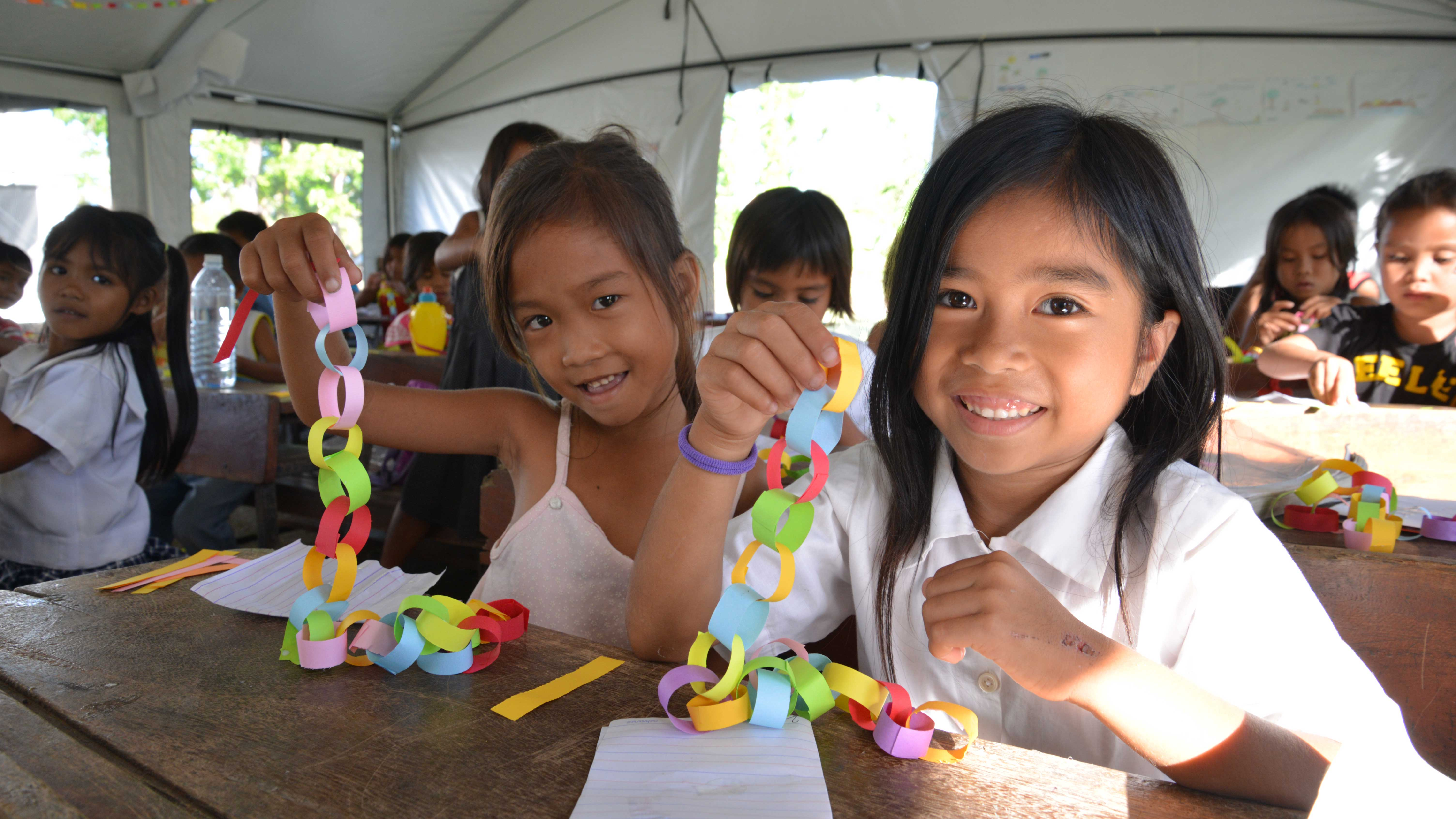 "Amamae and Jecel, whose homes were destroyed by Typhoon Haiyan, display the Christmas decorations they made at a World Vision's Child Friendly Space, which has helped over 1,400 children affected by the typhoon. ""I wish my home gets fixed,"" says Jecel."