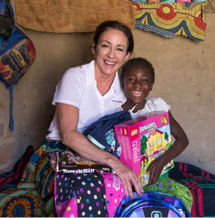 Actress Patricia Heaton meets her World Vision sponsored child 8-year-old Gracious, in Hamaundu, Zambia. Sponsor a child, sponsoring a child, child sponsor, celebrity ambassador