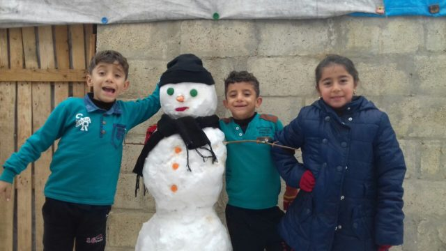 Children in A'zaz camp enjoy a light moment in the snow after fleeing violence in Syria. The camp is located about 60 miles from Aleppo City center. World Vision is providing blankets, mattresses and heating supplies to families there. PHOTO: World Vision.