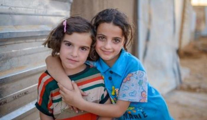 Sedra, 7, with her friend. The two children live at Jordan's Za'atari Refugee Camp, set up to accommodate the flow of Syrians fleeing violence in their homeland.
