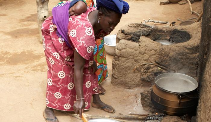 In Mali, a mother prepares food for her child. The effects of armed conflict and the 2012 food crisis have combined with the recent poor harvests to put the country on the brink of another food crisis.