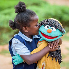 Girl hugs a muppet.