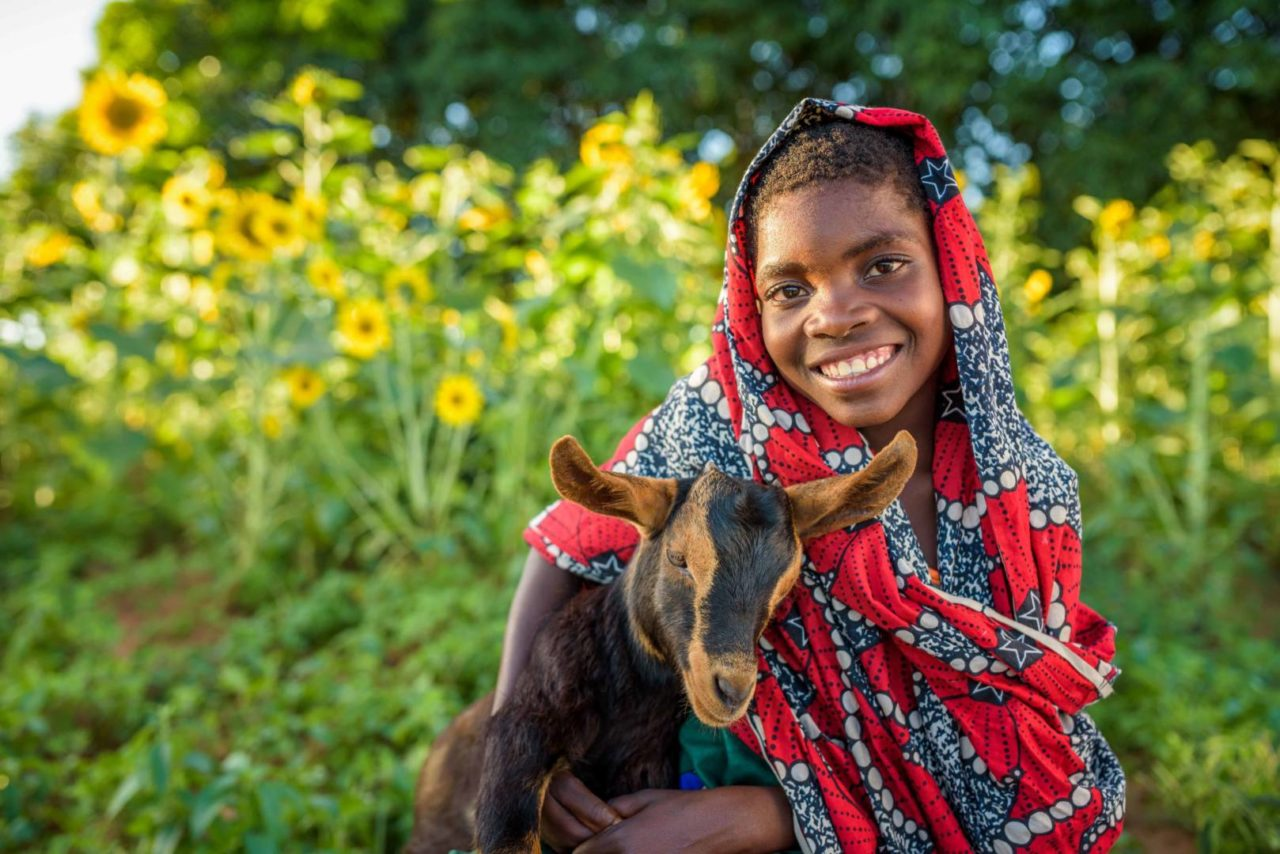Rosemary poses with a goat that was given to her family through World Vision's gift catalog