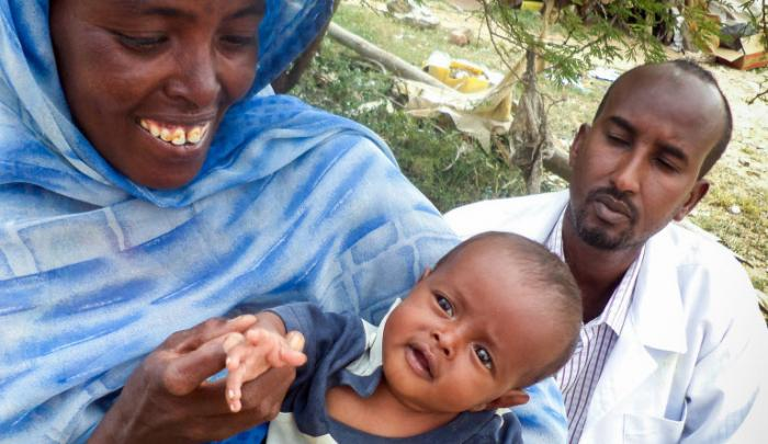 A young boy named Drisak, at home with his mother and a World Vision nutritionist during a regular home visit to monitor progress. PHOTO: World Vision