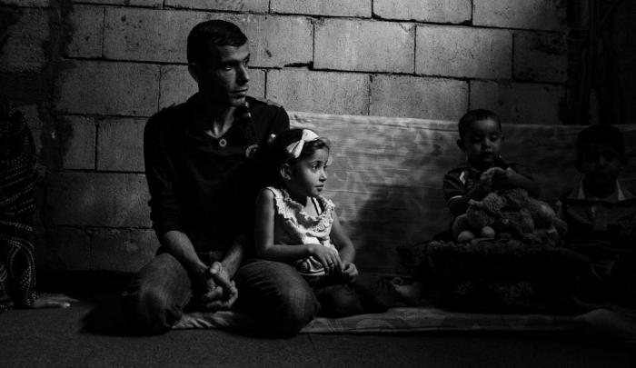 Syrian refugee Fatima, 8, with her father and younger brother Hakim. Eight-year-old Syrian refugee in Lebanon. The family left Syria after their home was hit by rockets. Some members of the family have lost their lives in the conflict