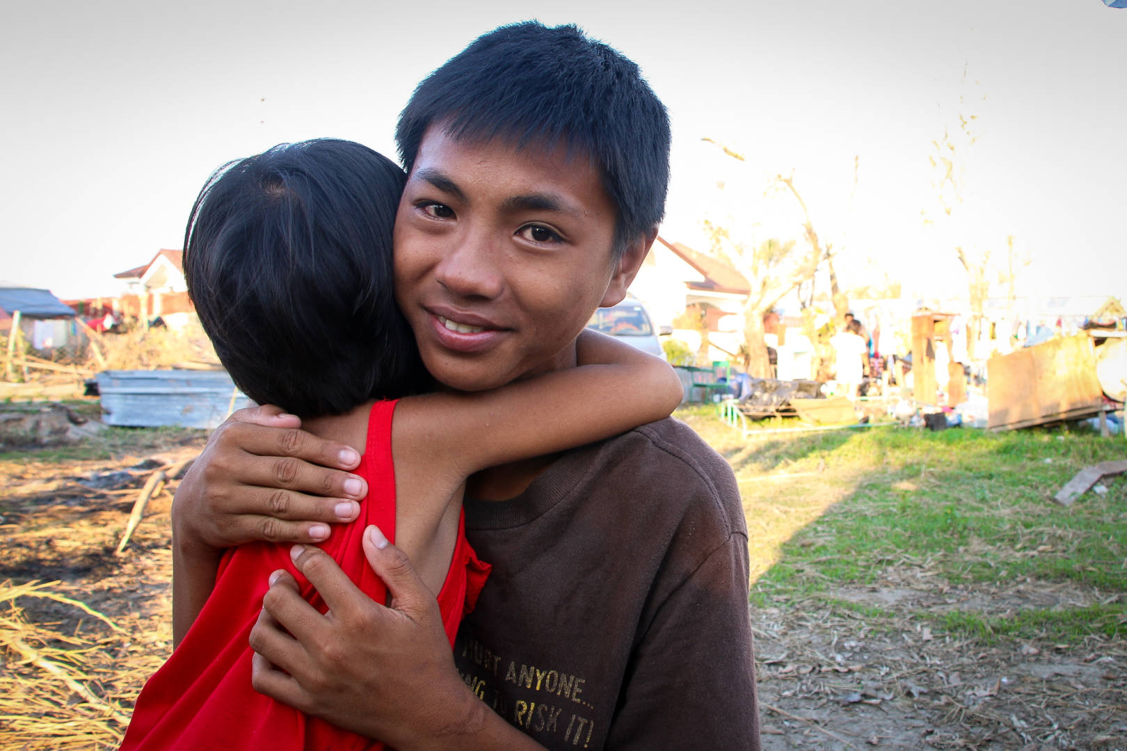 Standing near his home in the Philippines that was destroyed by Typhoon Haima in October 2016, Santiago holds his 4-year-old sister Princess. (©2016 World Vision, photo by Joy Malujo)