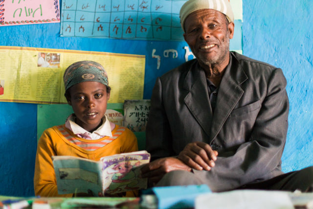 In Ethiopia, Seble and her grandfather share a book in the reading corner they made together. (©2015 World Vision, Max Greenstein)