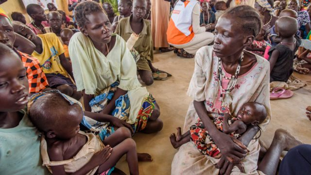Nyane, 2, sits on his sister's lap while waiting for World Vision staff to weigh and measure Nyane's nutritional status at a clinic in South Sudan.