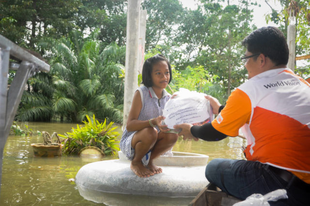 Man giving girl survival pack after deadly floods in Thailand.