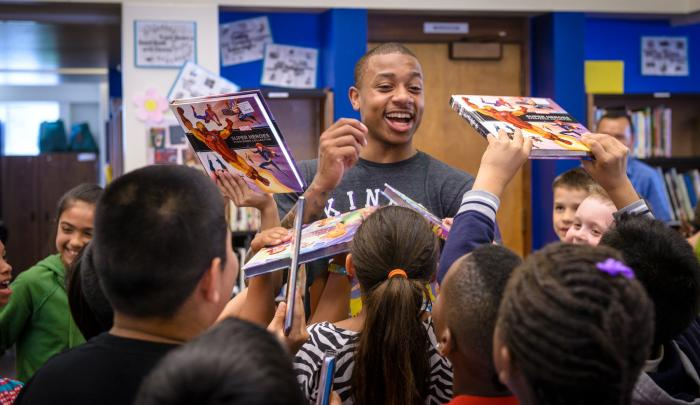 Boze Elementary School students ask NBA player Isaiah Thomas to autograph the new books they just received through World Vision. PHOTO: World Vision/Laura Reinhardt