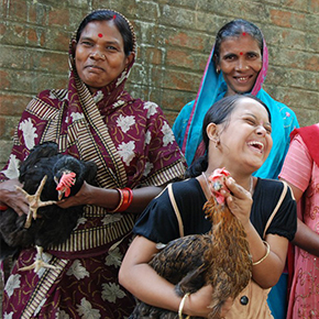Group of women holding chickens and smiling for the photo.
