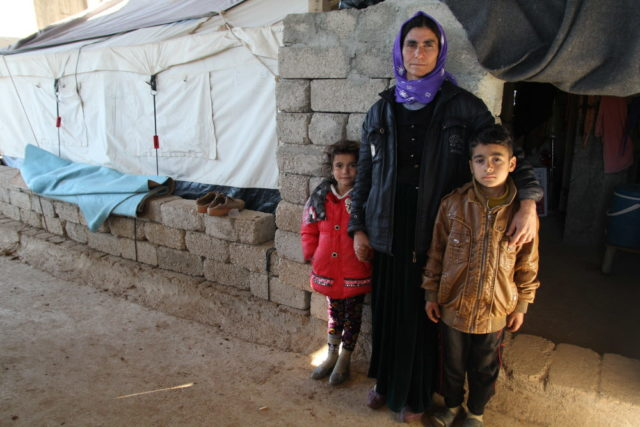 "Mayan, 46, and her children, Hareman, 6, (left), and Manaa, 8, (right), stand outside a concrete building in the Kurdistan Region of Iraq. They live in a tent pitched inside the shell of the structure. ""When we first arrived at this unfinished building (August 2014), we just slept on the ground,"" Mayan says. (©2015 World Vision, Suzy Sainovski)"