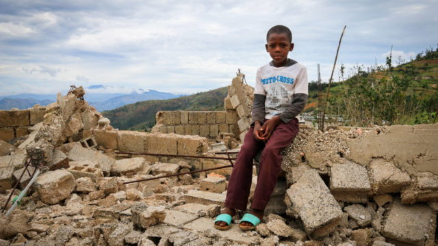 Haitian boy sits on the crumbled blocks that are all remaining of his family's home after Hurricane Matthew blew through Haiti