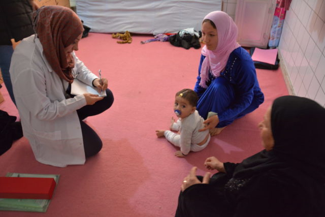 Dr. Maha talks to a mother and child during a visit to IDPs living in an abandoned hospital building. (©2015 Cecil Laguardia/World Vision)