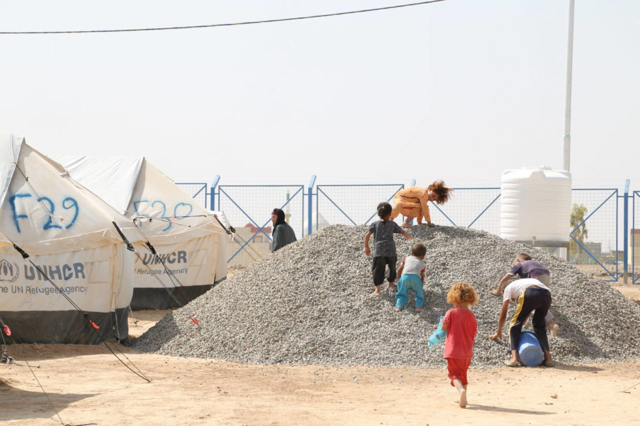 Children play in a gravel pile at Debaga camp for displaced people in Iraq. There is no safe place for them to play. (©2016 World Vision, Suzy Sainovski)