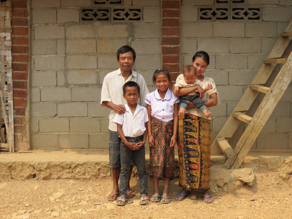 Kham and his family stand in front of his house