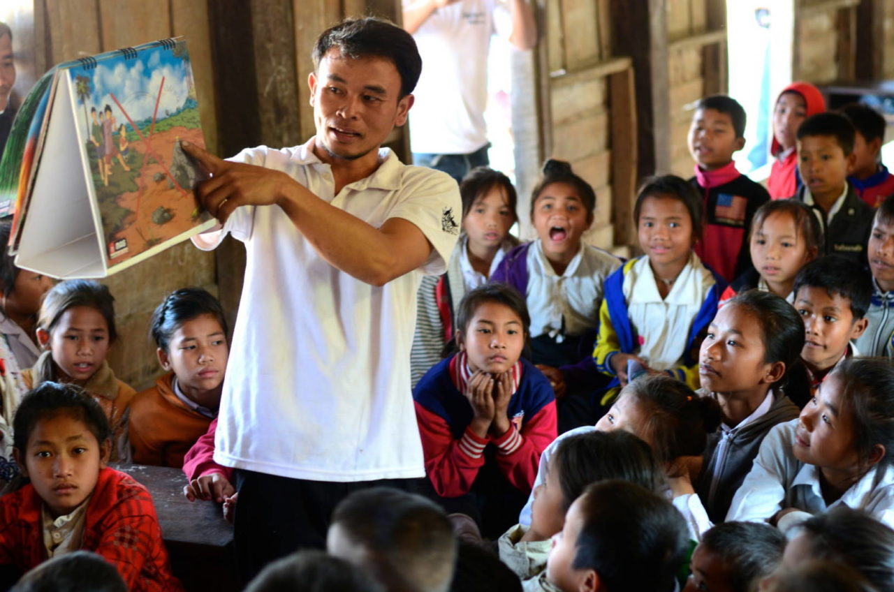 Phaytoun teaches school children about the dangers of aging bombs that are still found in the forest near his community in Laos. (©2015 World Vision, Mark Nonkes)