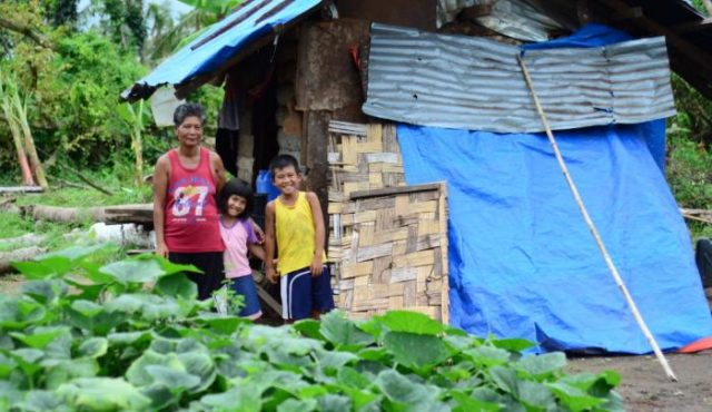 Norma and her children live inside a neighbour's house that is drenched everytime it rains. Their home was destroyed during Typhoon Haiyan. Since the storm, the children and their mother have been squatting in a neighbour's house that is covered by a worn-out tarpaulin. Now Norma's family will be receiving shelter material from World Vision to help them recover. PHOTO: Mark Nonkes/Worl