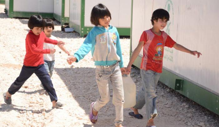 Children at Za'atari refugee camp in Jordan carry water.