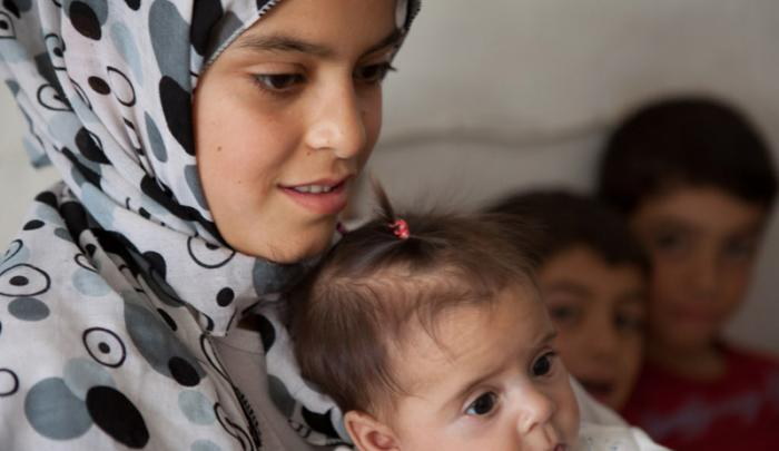 Rawan, 13, who fled Syria with her family; and her baby sister, Refef, who was born in the Za'atari refugee camp in Jordan.