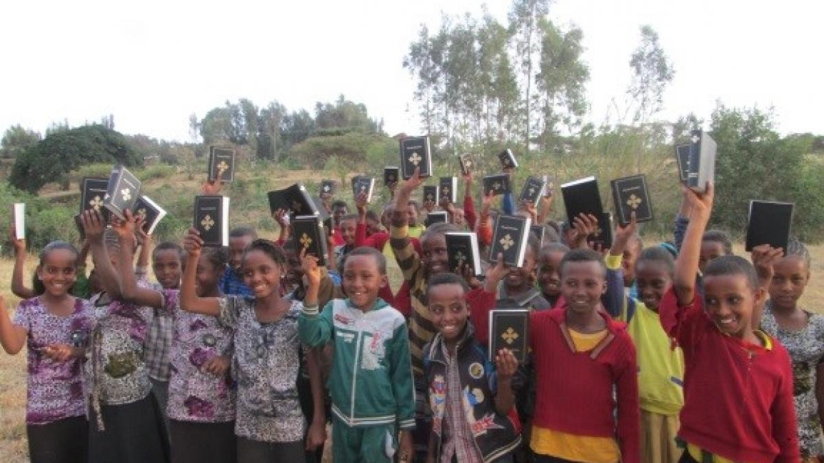 Sponsored children in Ethiopia hold up Bibles that they got as birthday gifts.