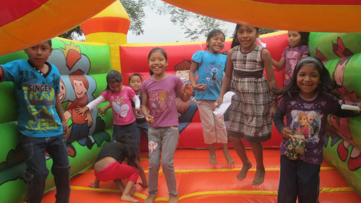 Sponsored children in Mexico jump in a bouncy castle at a community birthday party