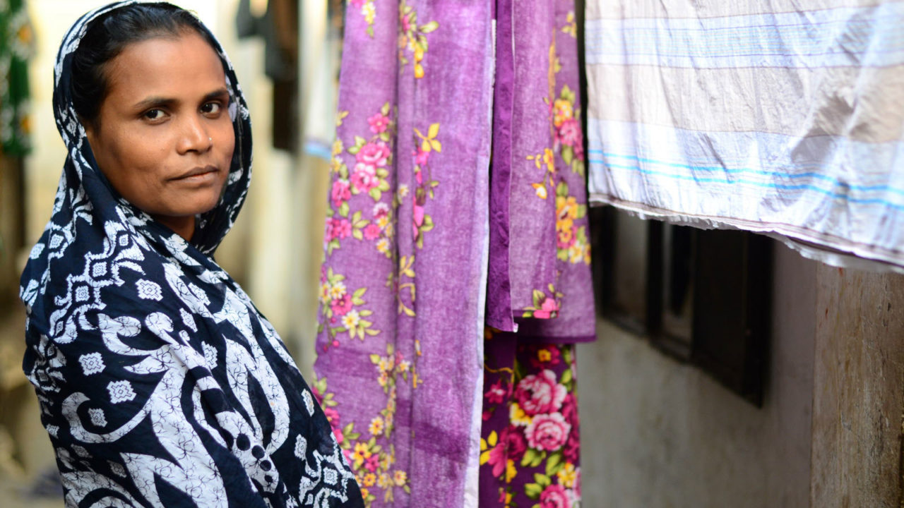 Bithi's mom stands in front of hanging laundry.