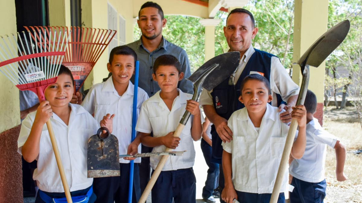 several students and teachers in Honduras stand holding their new tools