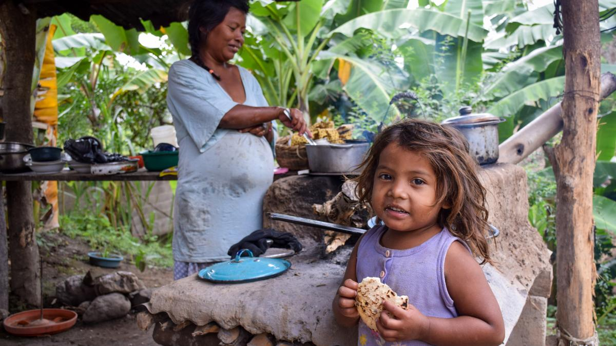 A pregnant mom and 4-year-old daughter stand at their outdoor kitchen