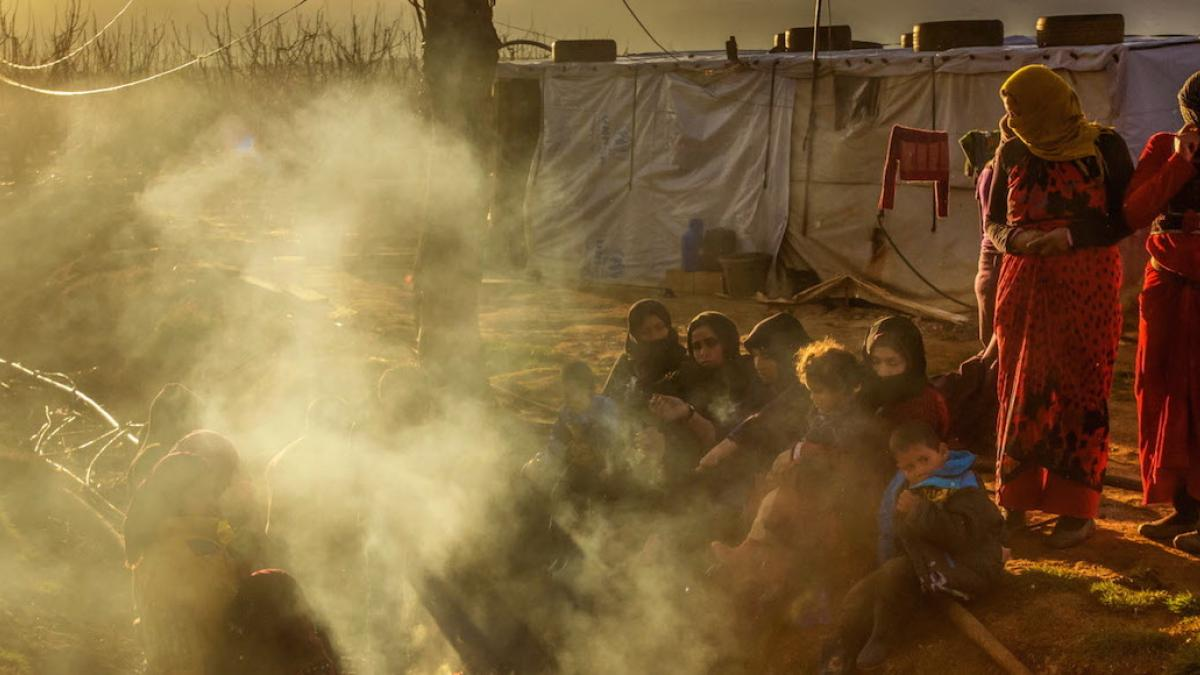 Refugees try to keep warm by burning trash (mostly plastic) in a tent settlement in West Bekaa, Lebanon, near the Syrian border. (© 2016, Jon Warren | World Vision)