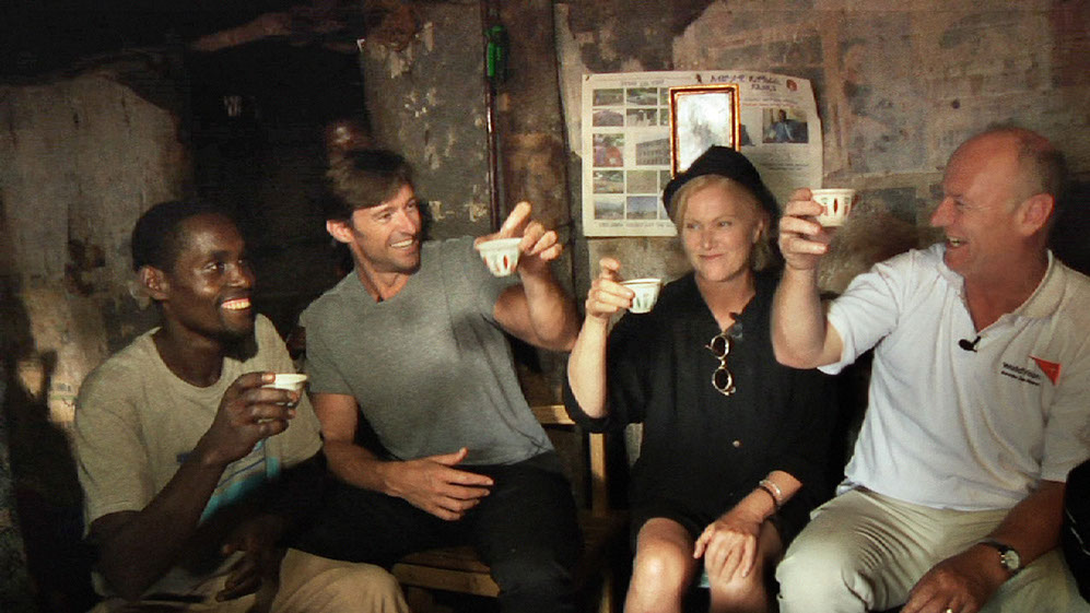 Dukale, Hugh, Deb, and Tim drink coffee in Dukale's hut.
