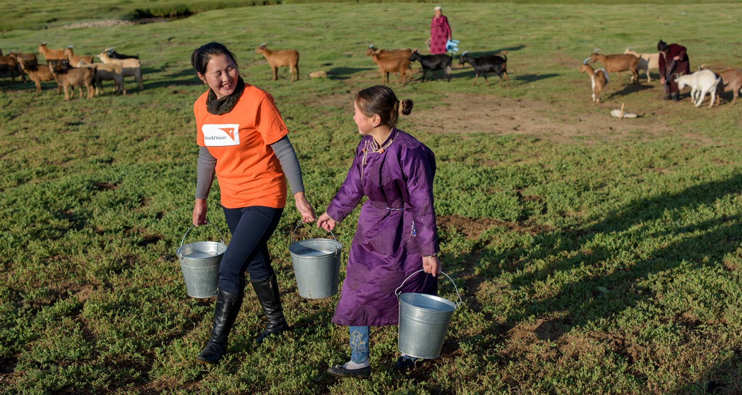 World Vision staff and Mongolian girl carry milk pails