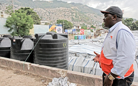 Theodore Scott, World Vision's water and sanitation manager, surveys water tanks at an displacement camp in Port-au-Prince, Haiti. Cholera spreads through contaminated water. PHOTO: Meg Sattler / World Vision