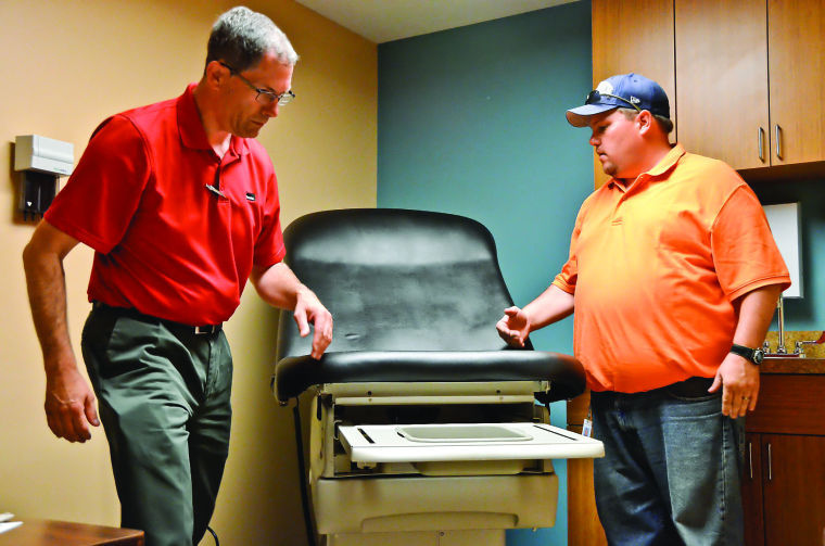 Midmark Corp. community relations manager Mitch Eiting, left, and World Vision warehouse manager Kevin Jones install a barrier-free exam table that was donated to Health Access Inc. in Clarksburg, WV.