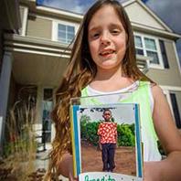 Sponsor holding photo of sponsored child.